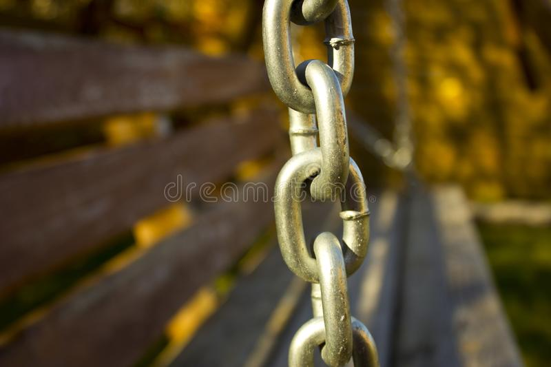 The element of the metal chain, as a decoration to the swings in the territory of the house for the rest. Metal chain on the street swing in the background of stock photography