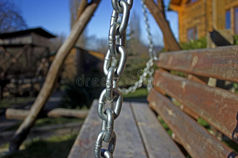 The element of the metal chain, as a decoration to the swings in the territory of the house for the rest. Metal chain on the street swing in the background of stock photos