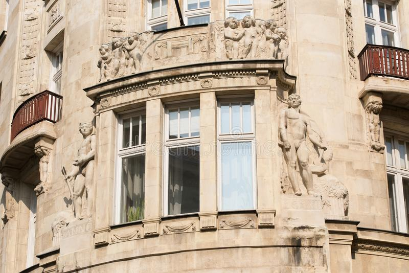 Element of an old building with a window and balconies. Decorated with bas-reliefs and sculptures stock image