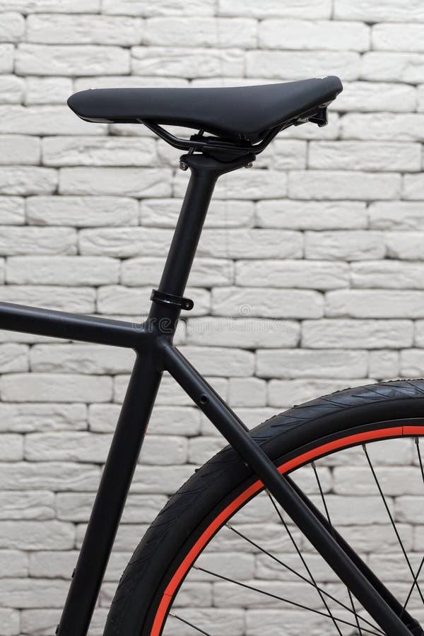 Element van een fiets Zwart zadel tegen een witte bakstenen muur stock afbeelding