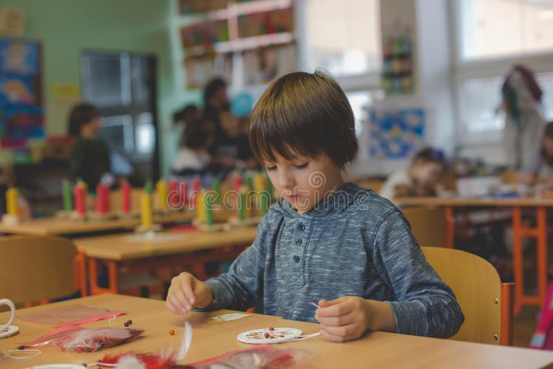 Elementair leeftijdskind, die kunst en ambachtproduct, droomvanger op school in kunstklasse creëren stock foto