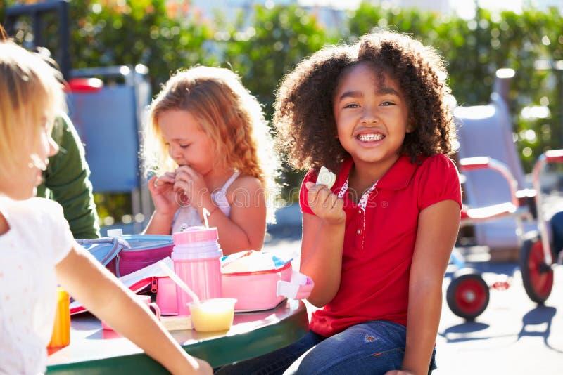 Elementaire Leerlingen die bij Lijst zitten die Lunch eten royalty-vrije stock foto's