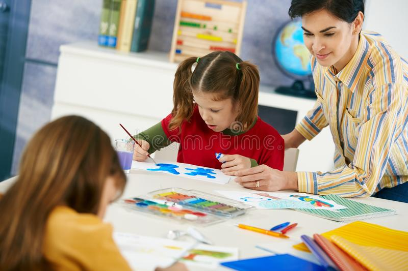 Children painting in art class at elementary school. Elementary age children sitting around desk enjoying painting with colors in art class in primary school royalty free stock image