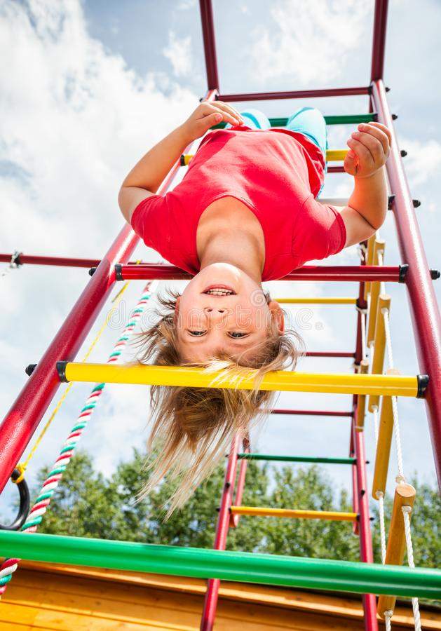 Little girl hanging from a jungle gym playing in a summer garden - child risky play concept. Elementary age girl hanging from a jungle gym monkey bars or royalty free stock photography