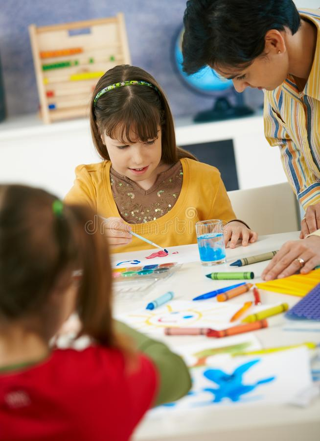 Elementary age schoolgirls painting stock images