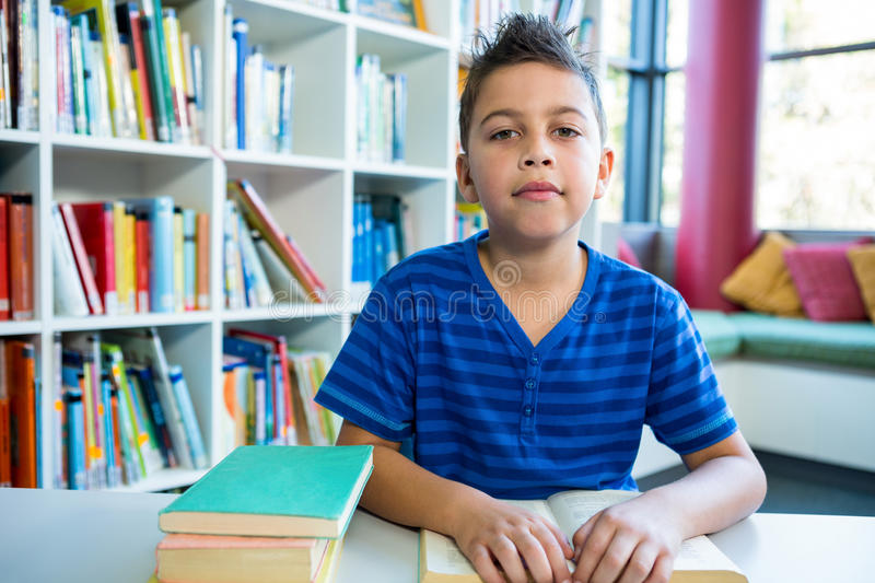Elementary boy reading book in school library stock photography