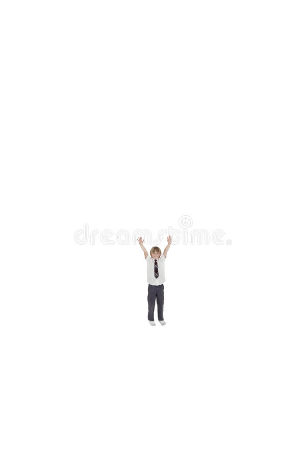 Elementary boy standing at distance with arms raised over white background