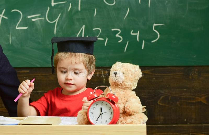 Elementary education concept. First former with toy on desk. Pupil in mortarboard, chalkboard on background. Boy on busy royalty free stock photos