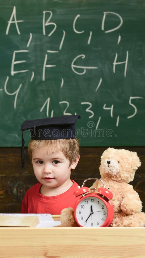Elementary education concept. Pupil in mortarboard, chalkboard on background. Kid studies near alarm clock and teddy royalty free stock photos