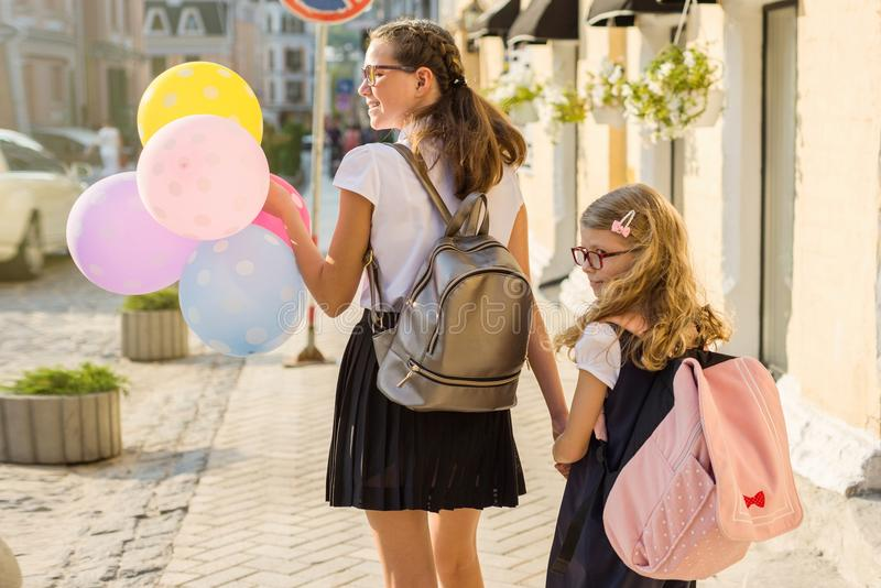 Elementary and high school students hold hands stock images