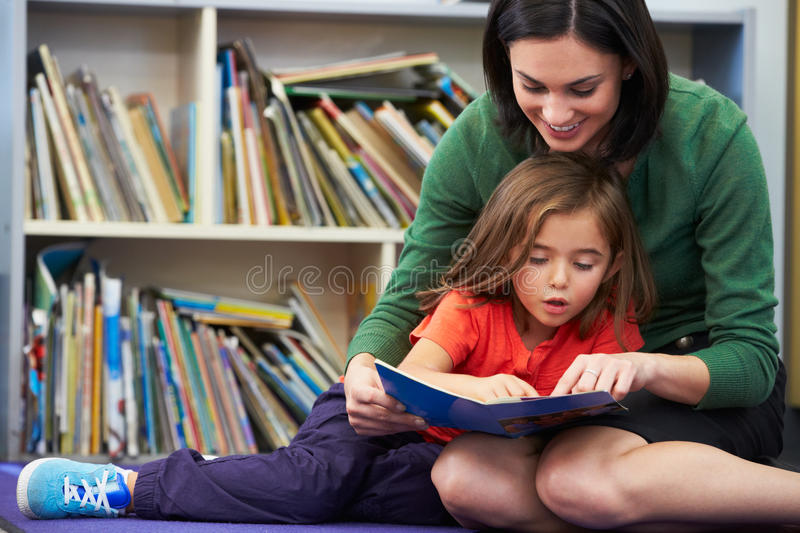 Download Elementary Pupil Reading With Teacher In Classroom Royalty Free Stock Image - Image: 30879826