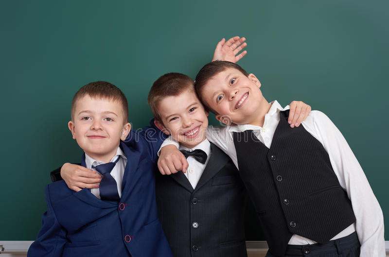 Elementary school boy fooling around near blank chalkboard background, dressed in classic black suit, group pupil, education conce. Pt stock image