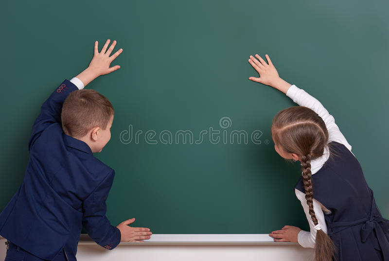 Elementary school boy and girl put hands on chalkboard background and show blank space, dressed in classic black suit, group pupil. Education concept royalty free stock photos