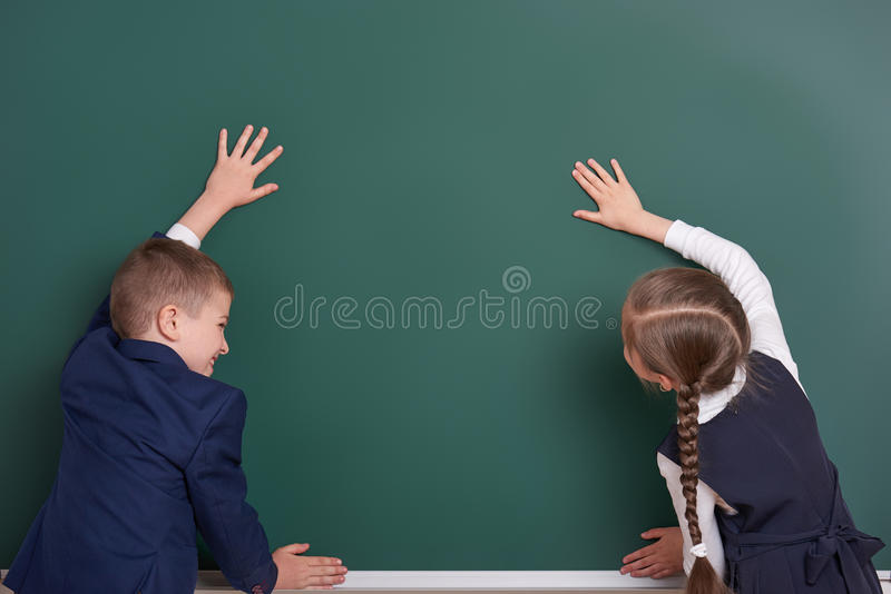 Elementary school boy and girl put hands on chalkboard background and show blank space, dressed in classic black suit, group pupil. Education concept royalty free stock images