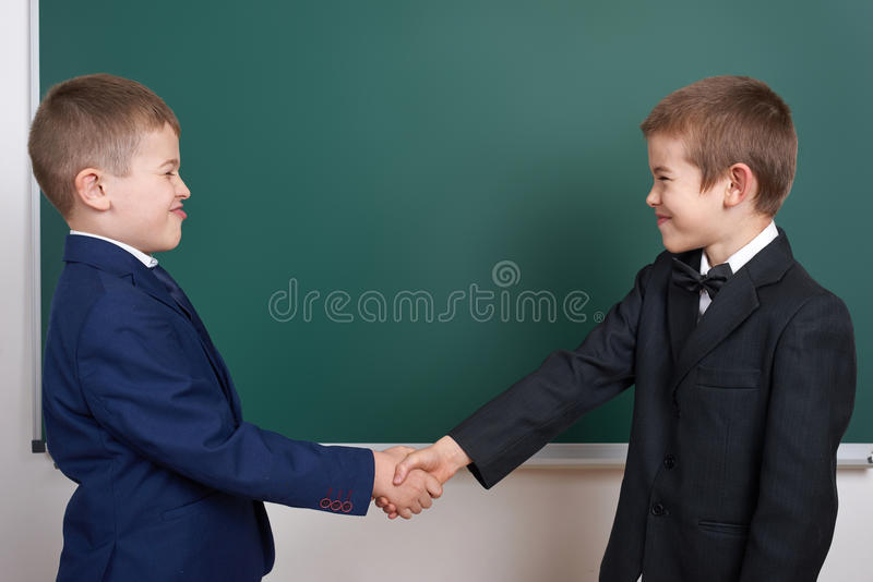 Elementary school boy near blank chalkboard background, dressed in classic black suit, group pupil, education concept royalty free stock photos