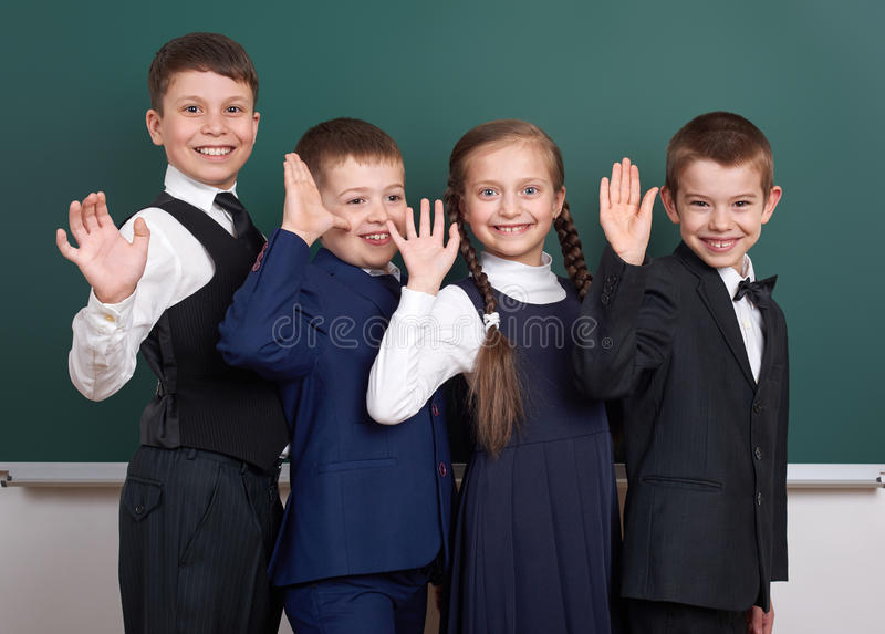Elementary school boy near blank chalkboard background, dressed in classic black suit, group pupil, education concept stock images
