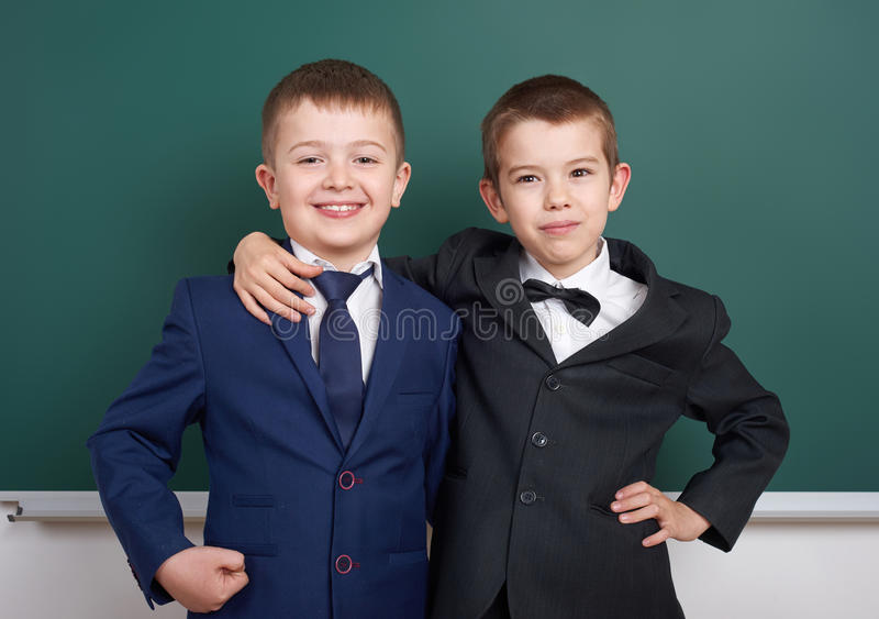 Elementary school boy near blank chalkboard background, dressed in classic black suit, group pupil, education concept stock image