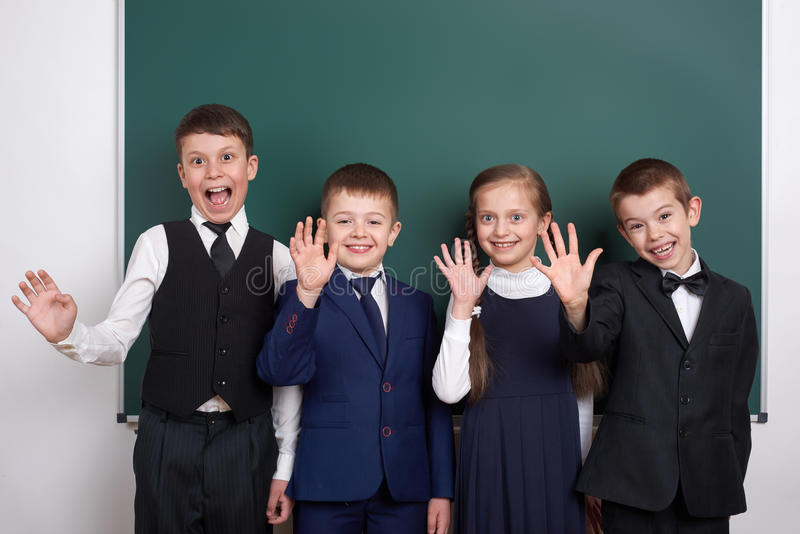 Elementary school boy near blank chalkboard background, dressed in classic black suit, group pupil, education concept royalty free stock photo