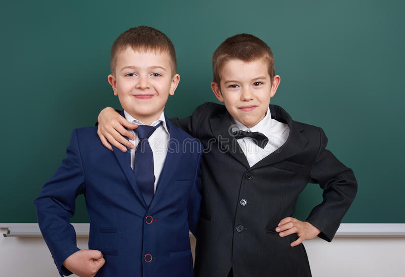 Elementary school boy near blank chalkboard background, dressed in classic black suit, group pupil, education concept stock photo