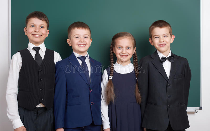 Elementary school boy near blank chalkboard background, dressed in classic black suit, group pupil, education concept stock photography