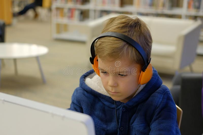 Elementary school boy sitting in library, using touchscreen computer for education stock images