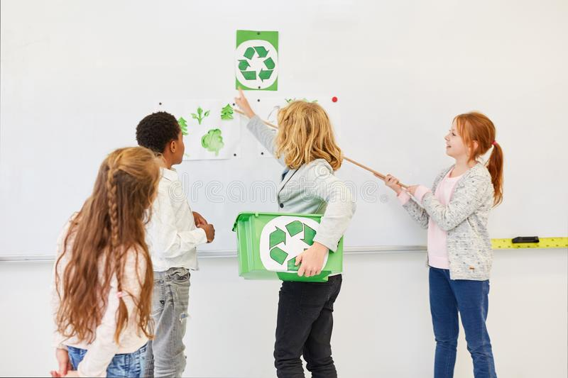 Children give a talk on recycling. Elementary school children hold a team talk about a recycling project royalty free stock images
