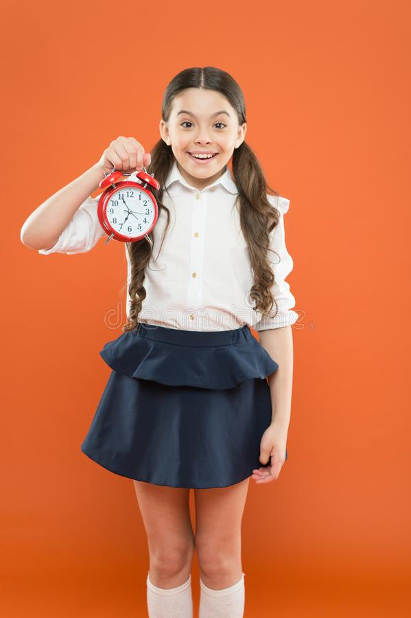 Elementary school day bell schedule. Schooltime concept. Avoid being late. Schoolgirl hold alarm clock. Time to study. Classes begin. Developing discipline royalty free stock images