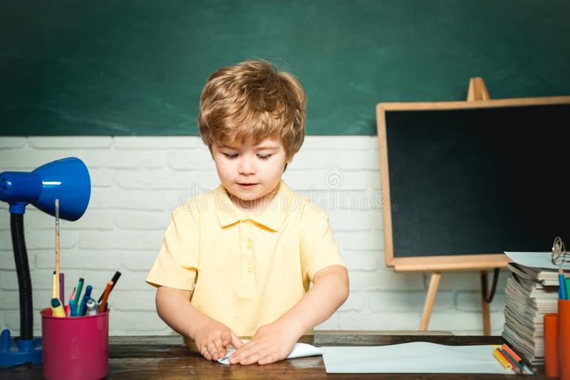 Elementary school and education - school concept. Kid with a book. Funny little child having fun on blackboard stock images
