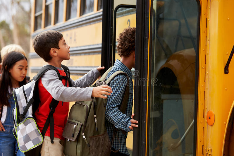 Elementary school kids climbing on to a school bus royalty free stock images