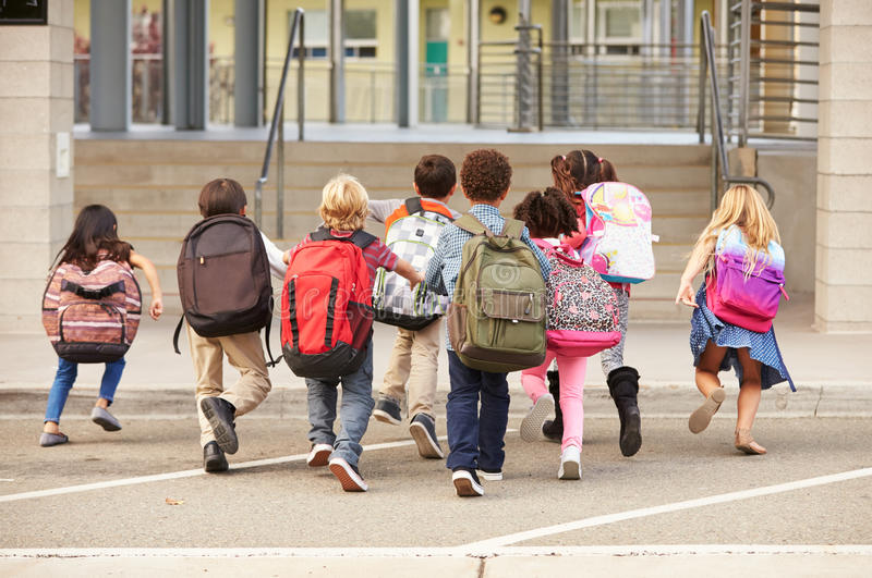 Elementary school kids running into school, back view stock images