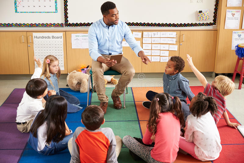 Elementary school kids sitting around teacher in a lesson royalty free stock images