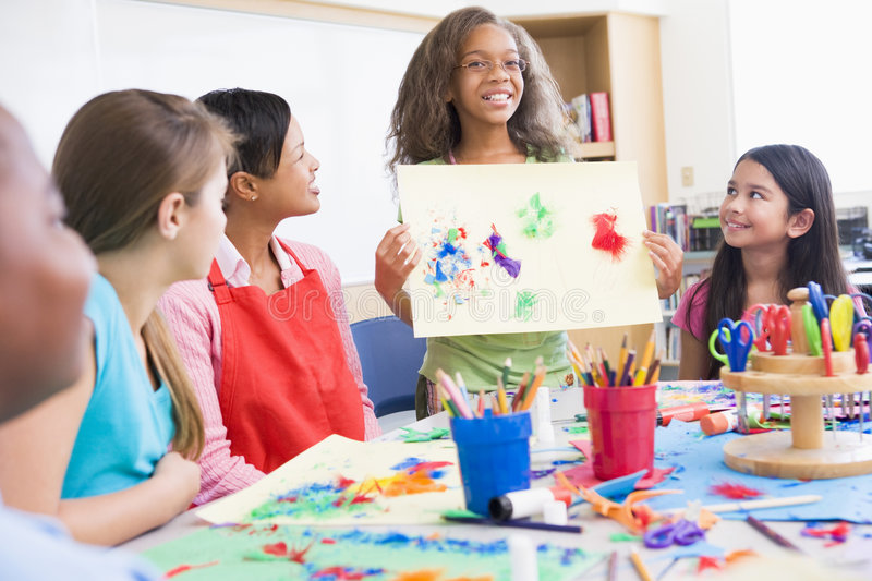 Elementary school pupil in art class. Elementary school pupil discussing picture with classmates royalty free stock photography