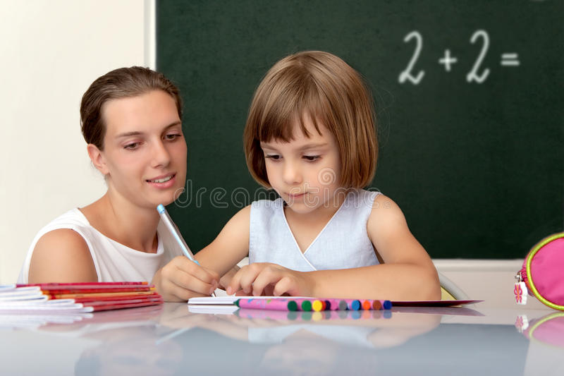 Elementary school pupil working with teacher