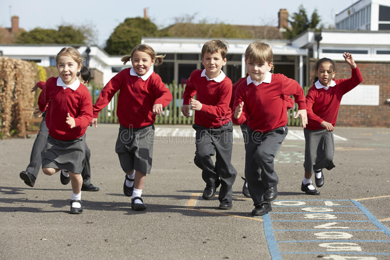 Elementary School Pupils Running In Playground royalty free stock photography