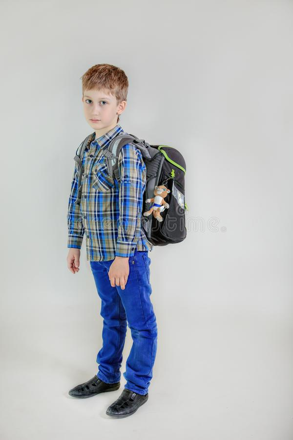 Elementary school student with backpack isolated on gray background. Cute boy depicted in height stock photography