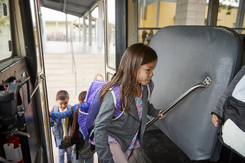 Elementary schoolgirl getting on the school bus to go home royalty free stock photos