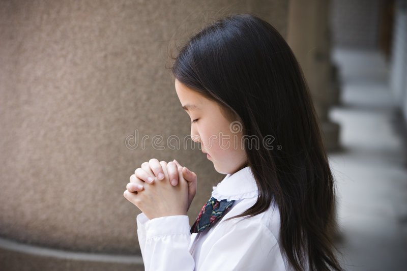 Elementary schoolgirl praying stock image