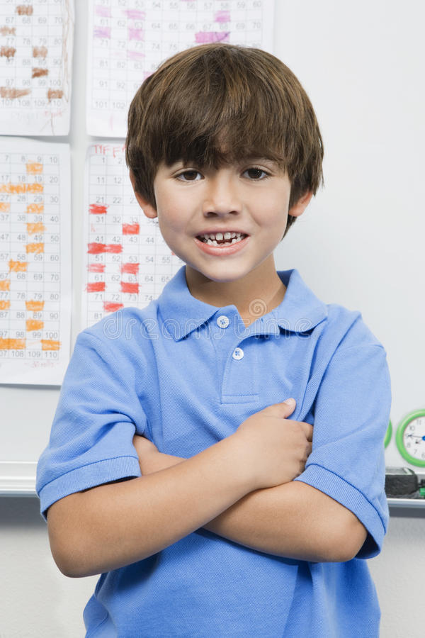 Elementary Student In Classroom. Portrait of an elementary student standing with arms crossed in classroom royalty free stock photo