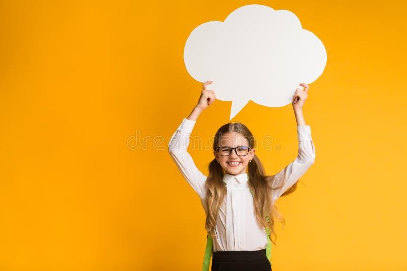 Elementary Student Girl Holding Speech Bubble Overhead, Studio Shot arkivfoton