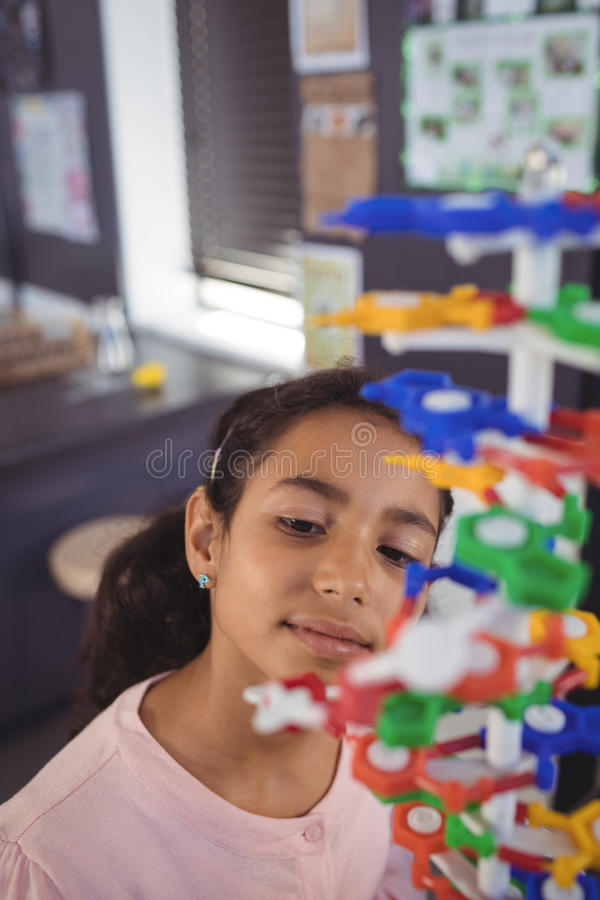 Elementary student looking at model in classroom stock image