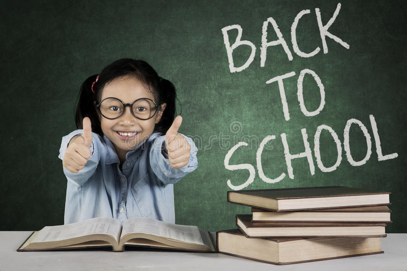 Elementary student shows ok sign in classroom stock photography