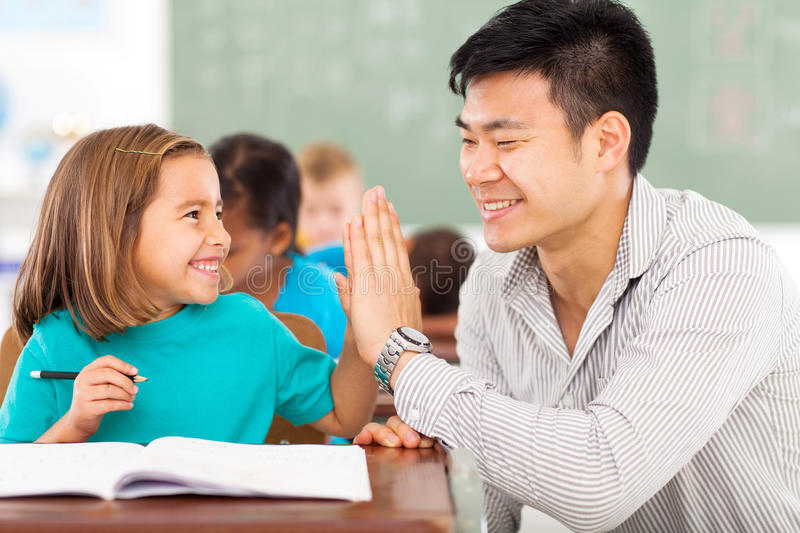 Elementary teacher student. Cheerful elementary school teacher and student high five in classroom stock photo