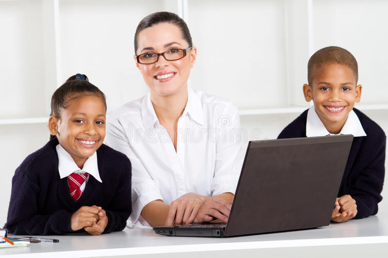 Elementary teacher students. Elementary teacher teaching computer class to students stock images