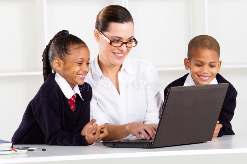 Elementary teacher teaching computer royalty free stock image