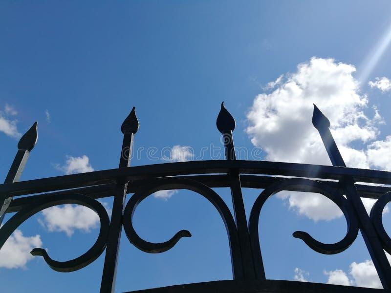 Elementen van metaal zwarte omheining tegen blauwe hemel en witte wolken royalty-vrije stock fotografie