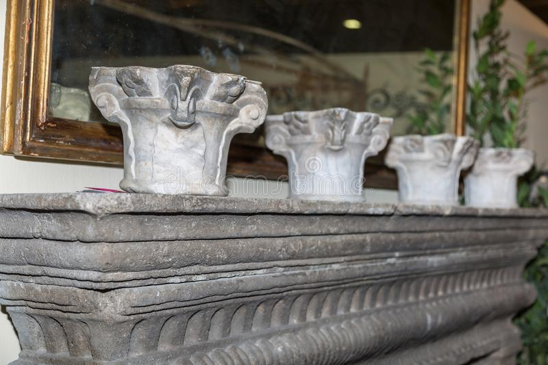 Elementi del capitale di colonna sullo scaffale di pietra e su uno specchio dietro immagine stock libera da diritti