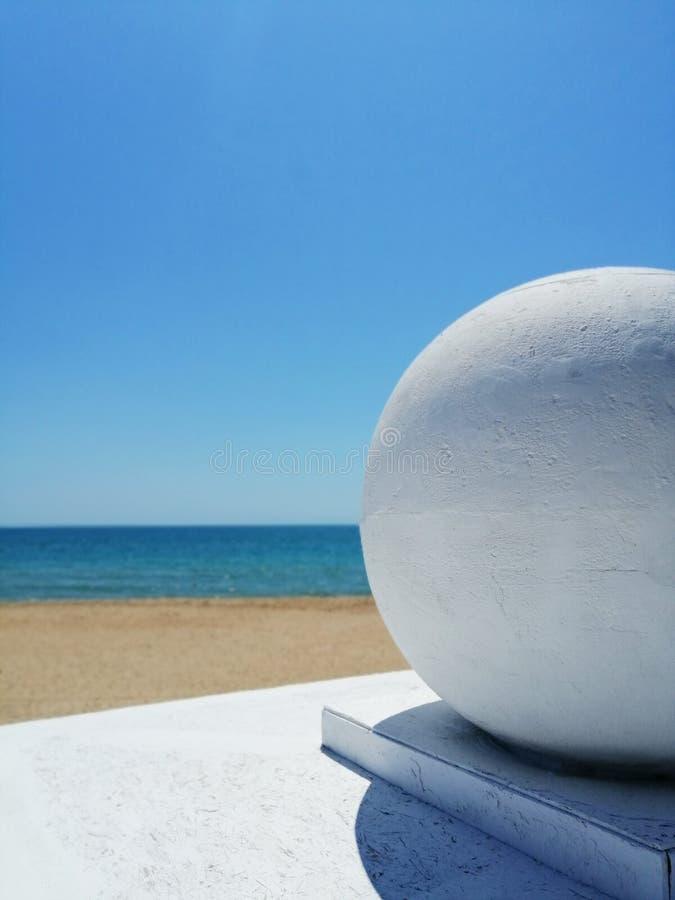 Elemento arquitetónico - uma bola branca no fundo do mar, da areia e do céu fotografia de stock royalty free