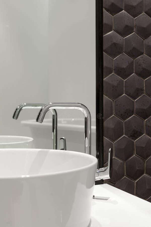 Elemento dell'interno del bagno con il lavandino bianco ed il grande specchio Nuovo lavabo e mattonelle esagonali nere delle matt immagini stock libere da diritti