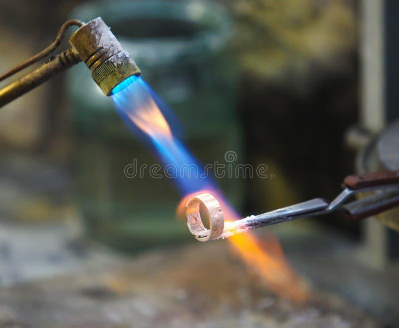 Elemento incandescente na forja no batente do ferro isolado imagem de stock
