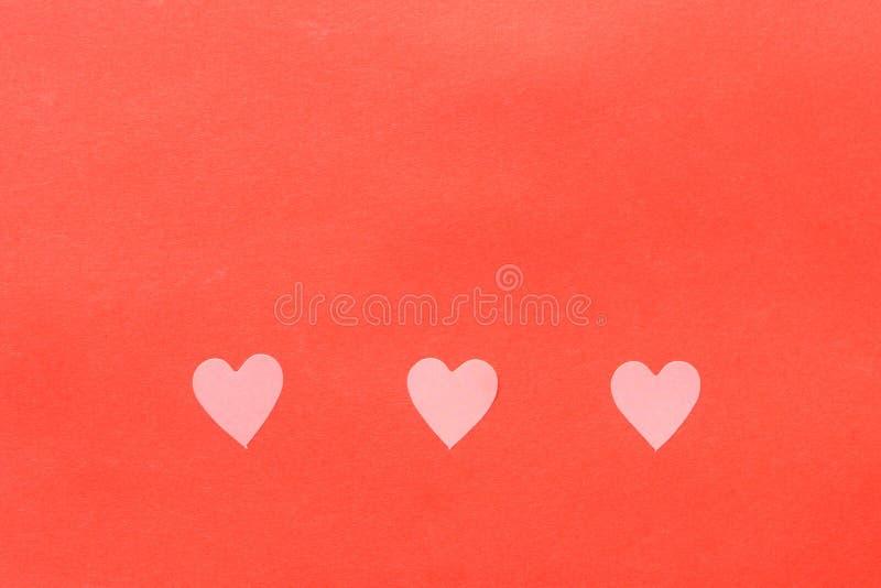 Elementos de papel en la forma del vuelo del coraz?n en fondo rosado imagen de archivo